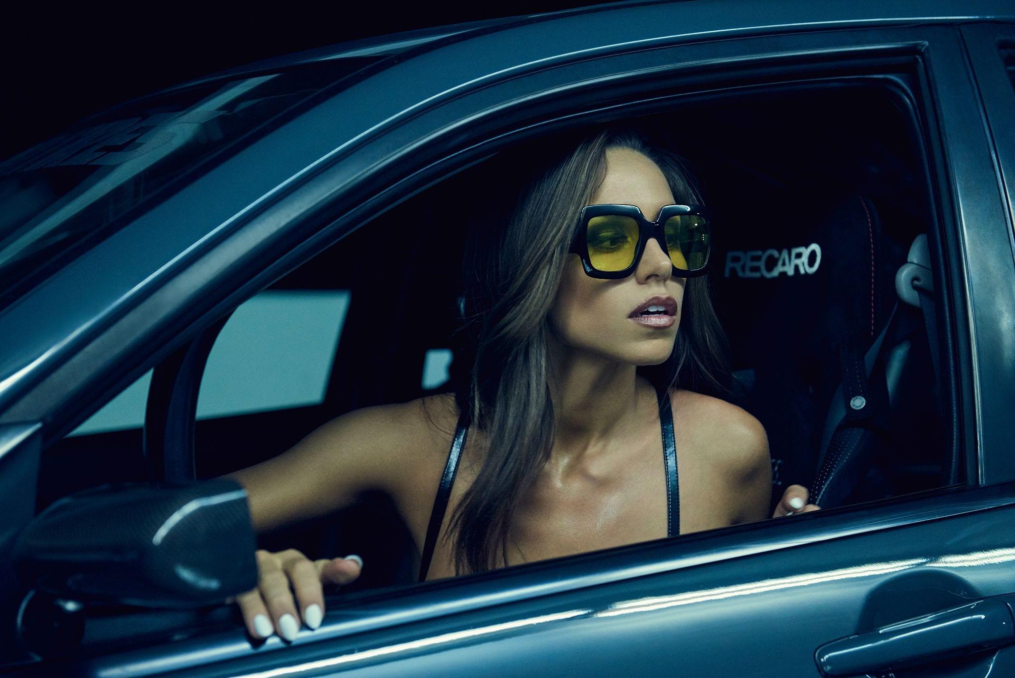 Photo of Model Kyra Keli wearing black glasses sitting in a grey car.